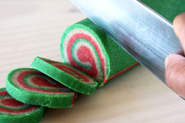 A log of unbaked pinwheel christmas nankhatai cookies being sliced with a large knife.