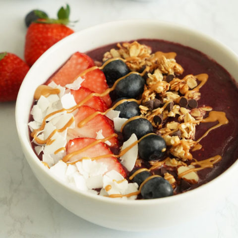 açaí bowl topped with coconut flakes, strawberries, blueberries, granola and peanut butter drizzle