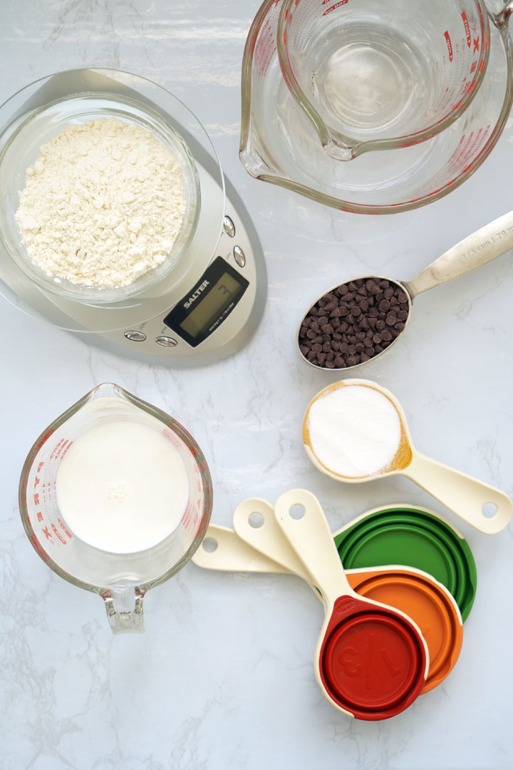 Top view of a digital food scale, various liquid measuring cups and dry measuring cups.