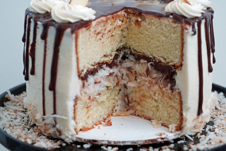 Sliced open almond joy cake showing the inside coconut and ganache filling layers.
