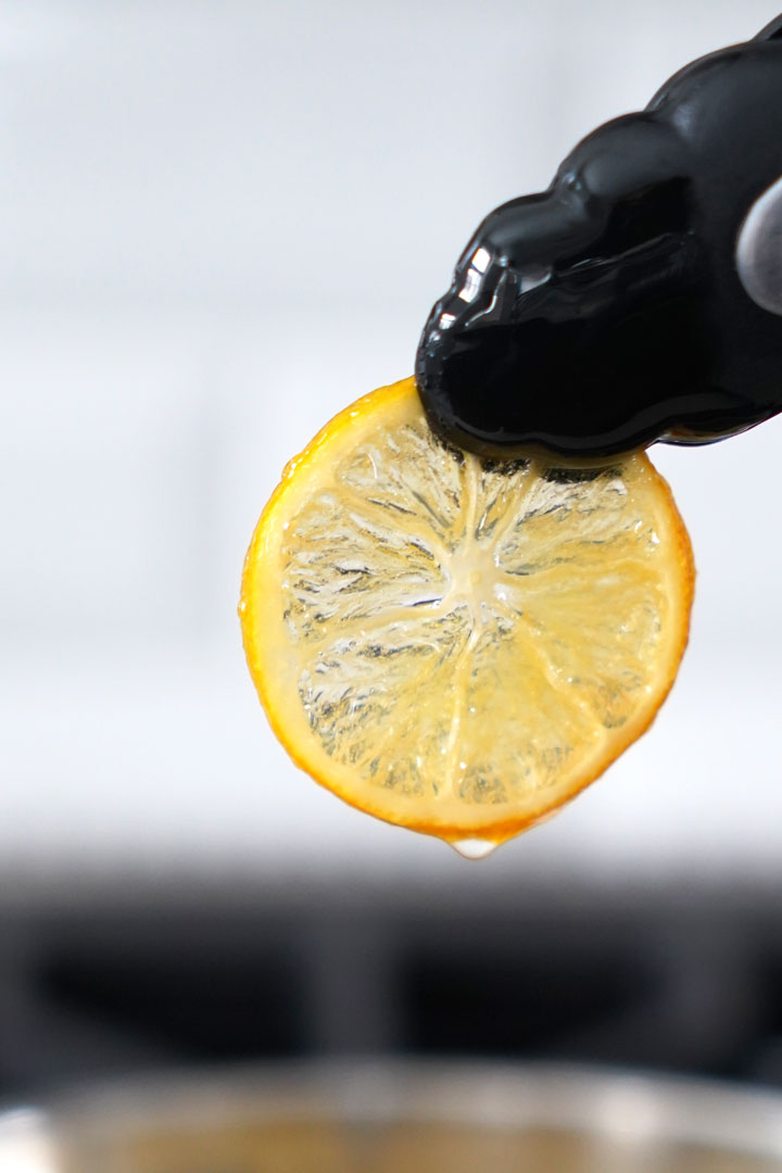 Close up of a candied lemon being pulled out of the pot with tongs.