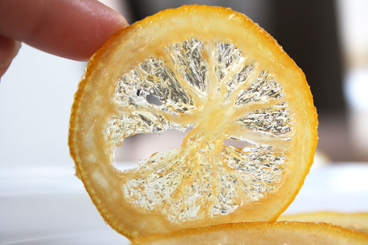 Candied lemon slice being held up by a finger.