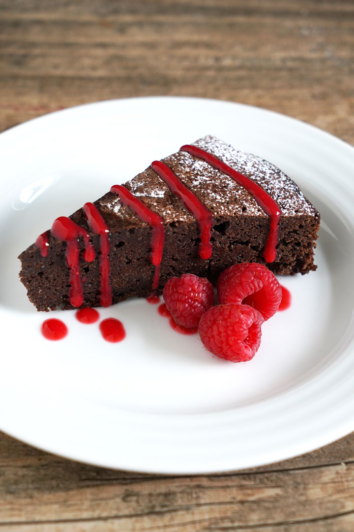 Chocolate cake slice with raspberry sauce drizzled over the top and fresh raspberries to garnish.