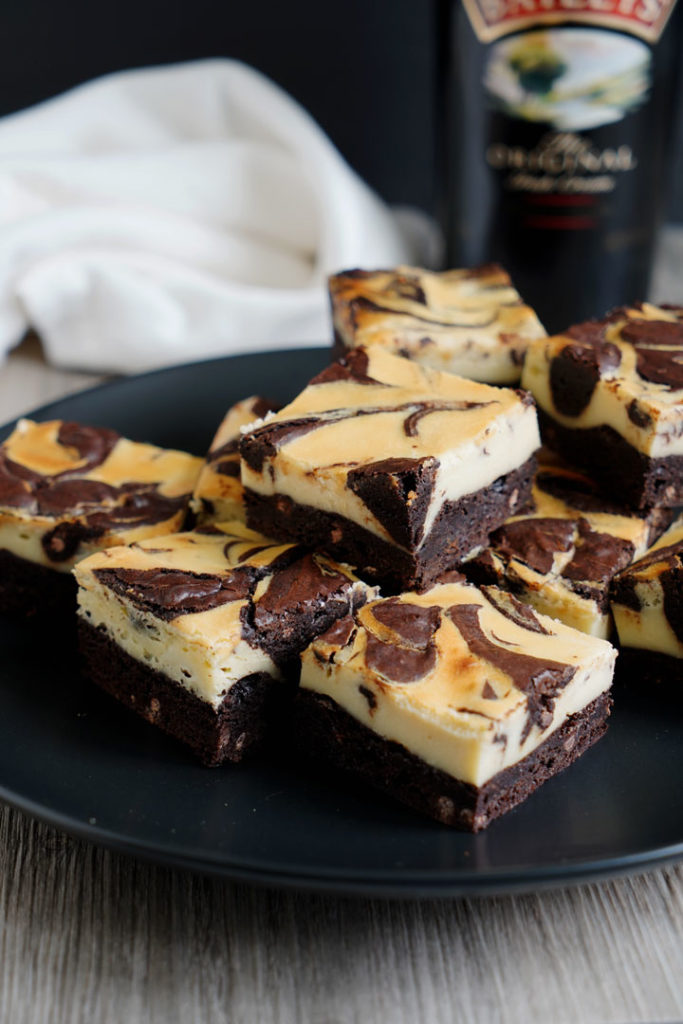 Irish cream cheesecake brownies on a black dish with Baileys bottle in background.