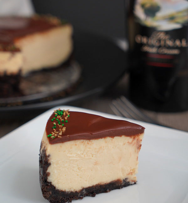 Slice of Baileys Cheesecake on white plate with cheesecake and bottle in background.