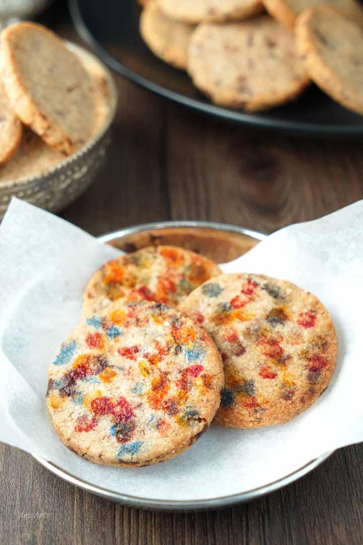 Colorful Holi cardamom cookies in a parchment paper lined silver bowl.