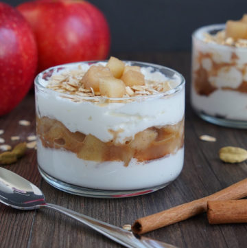 Cooked Apple parfait in small glass bowl with spoon on the side. Apples in background and cinnamon sticks in the foreground.