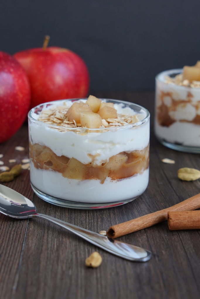 Apple Cinnamon Parfait in small glass bowl with spoon on the side. Apples in the background and cinnamon sticks in the foreground.