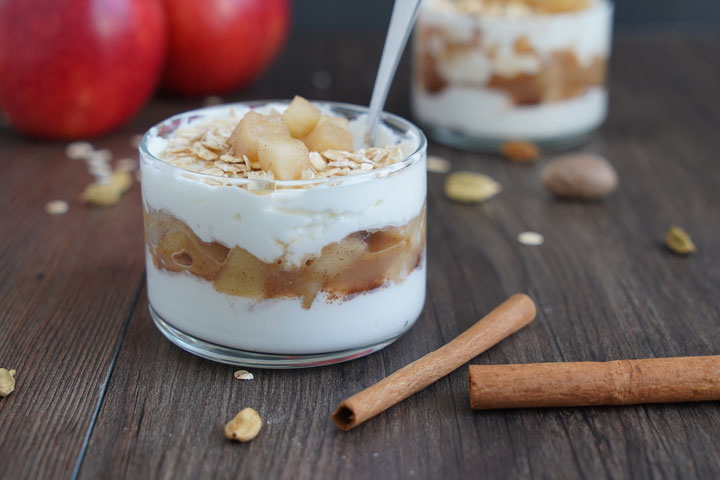 Apple Cinnamon Parfait in small glass bowl with spoon. Apples in the background and cinnamon sticks in the foreground.