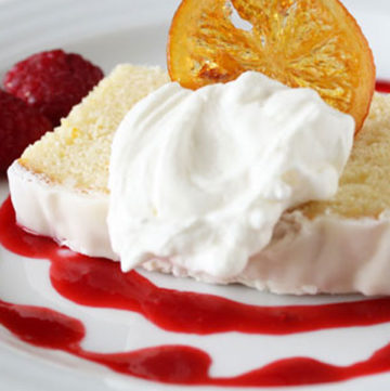 lemon poundcake slice plated with raspberry coulis, whipped cream and candied lemon slice.