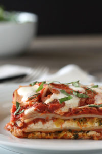 Slice of vegetable lasagna in a white plate with greens in a bowl in background.