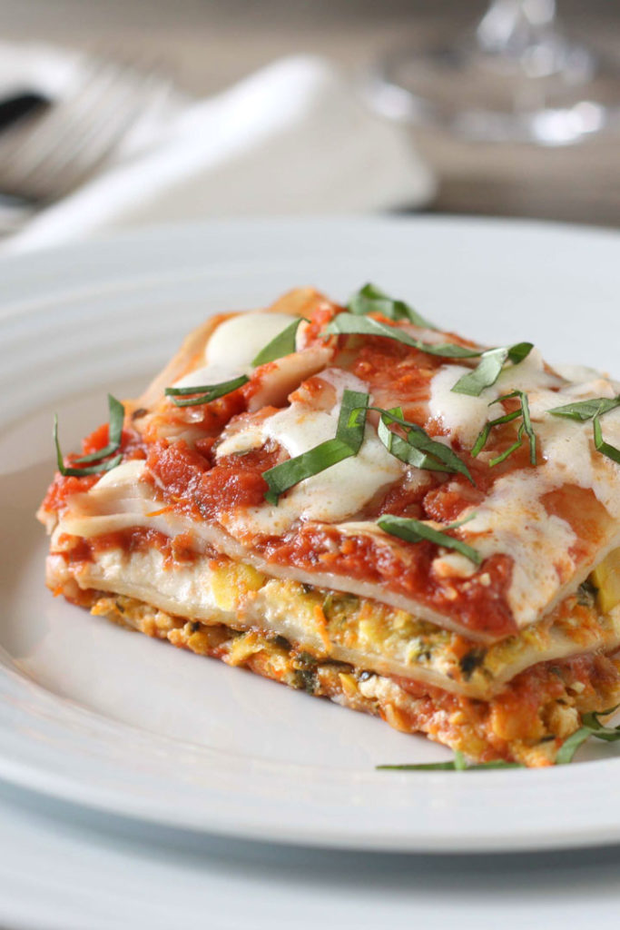 Slice of vegetable lasagna on white plate.