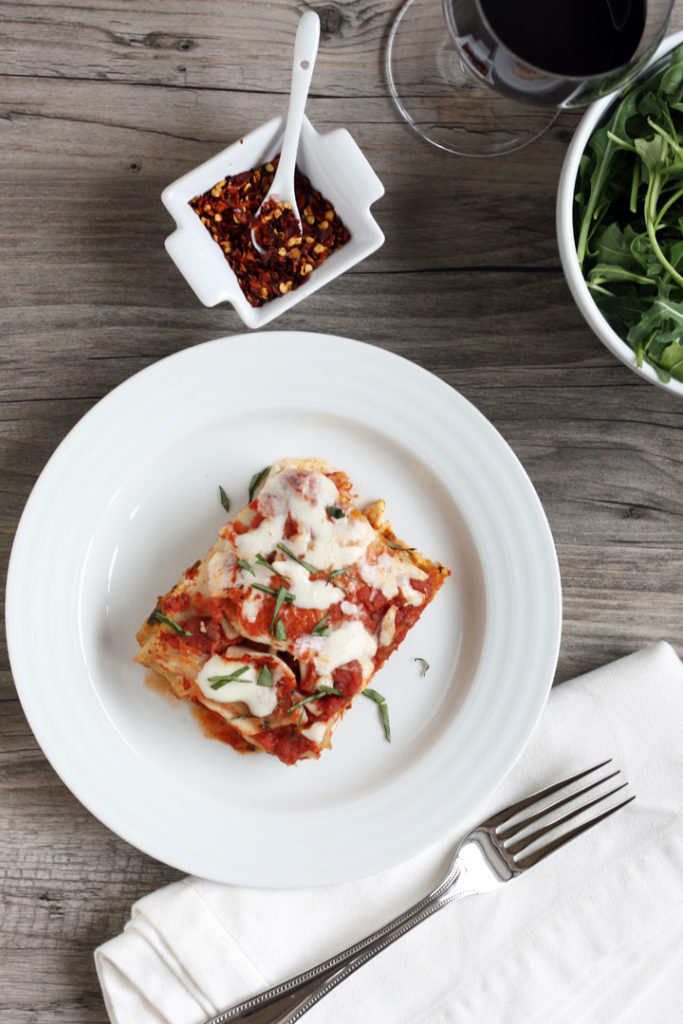 Overhead shot of vegetable lasagna slice, crushed red peppers in small dish and fork on napkin.