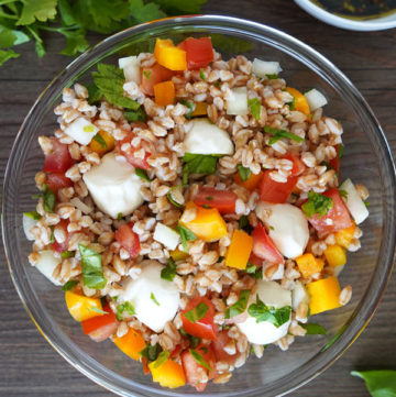 Italian herb farro in clear glass bowl, top view with cilantro and dressing on the side.