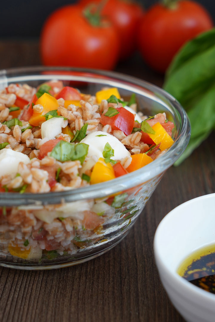 Italian herb farro in clear glass bowl with tomatoes in background.