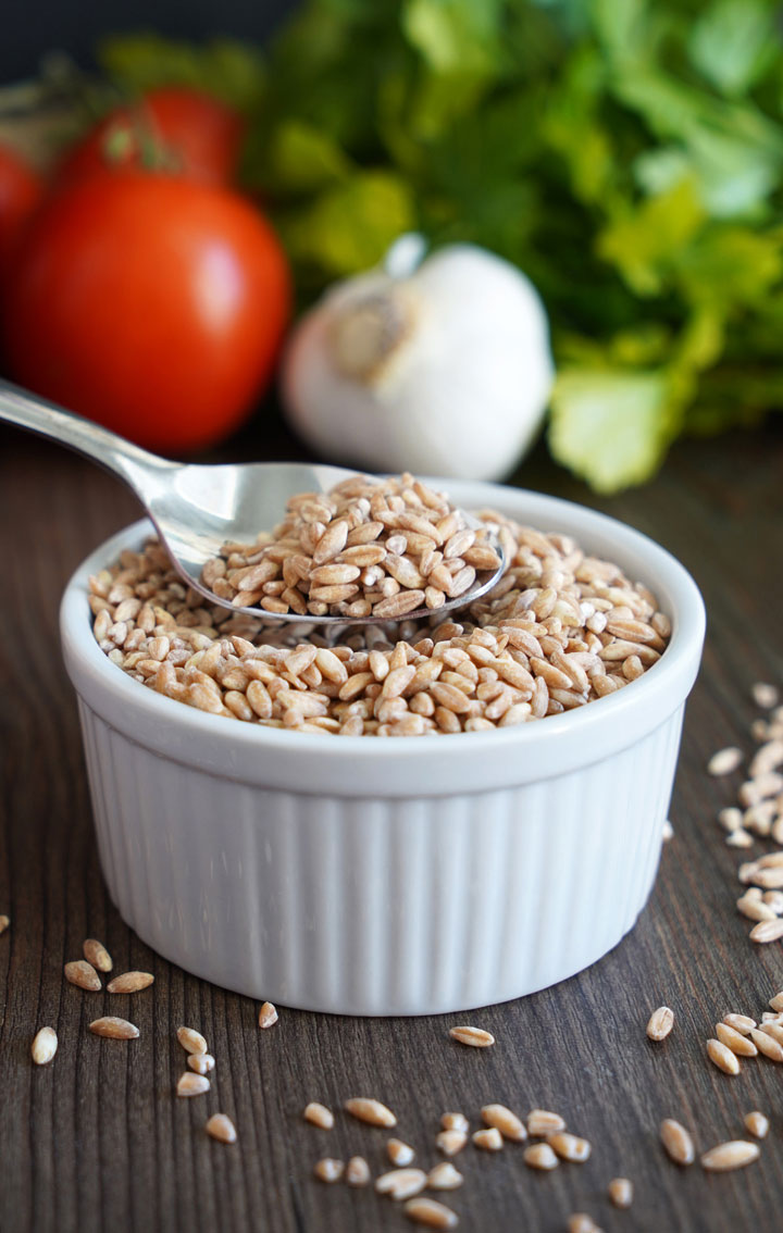 Uncooked farro in white bowl with spoon in farro and vegetables in the background.