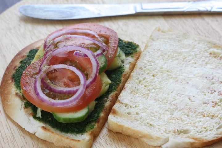 Open Bombay sandwich with chutney, potatoes, cucumbers, tomato, onions and masala.