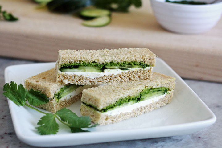 Three cucumber and mint cilantro chutney sandwiches  with cilantro garnish on a white square plate.
