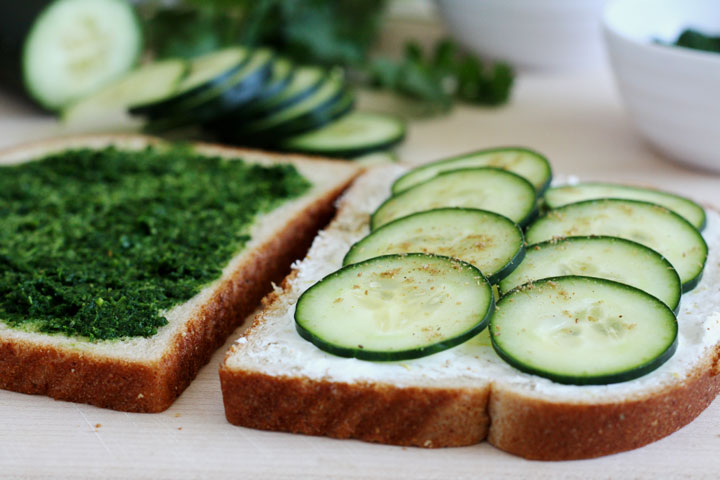 Bread slices with one showing cream cheese and cucumbers on top and the other spread with mint cilantro chutney.
