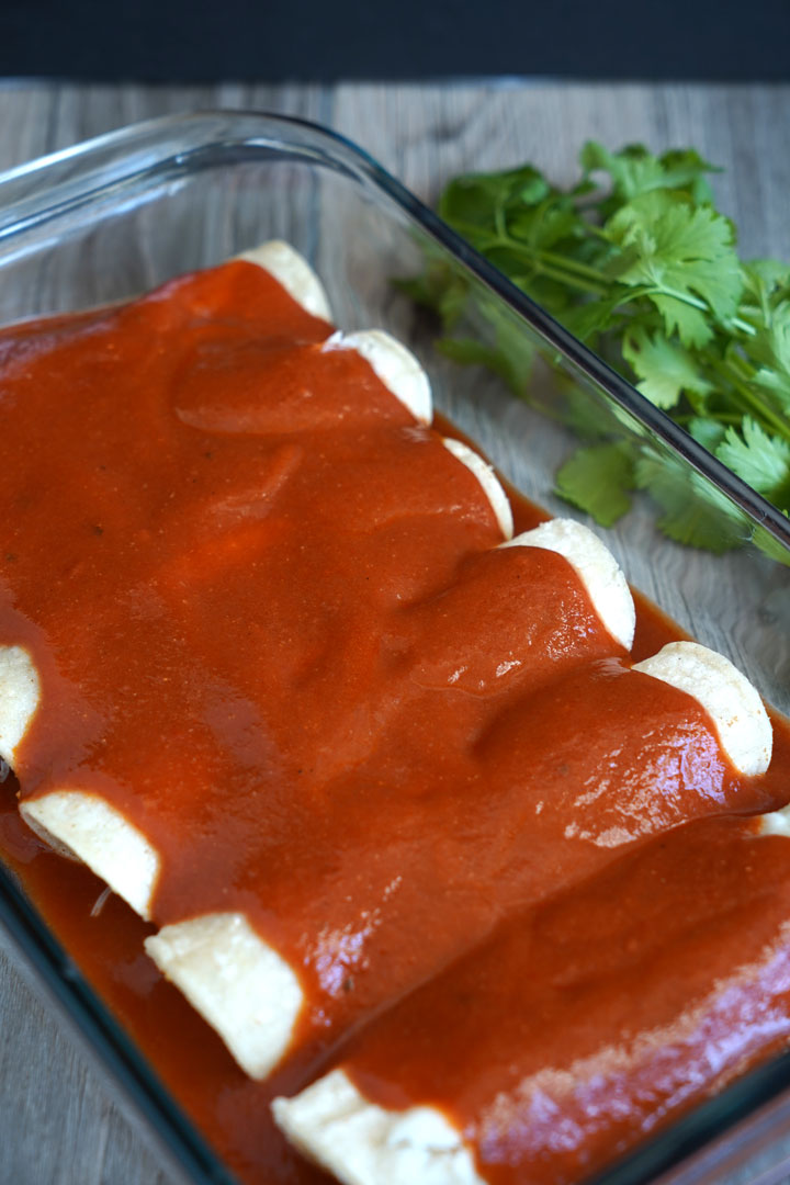 Enchilada sauce covering a tray of rolled enchiladas.