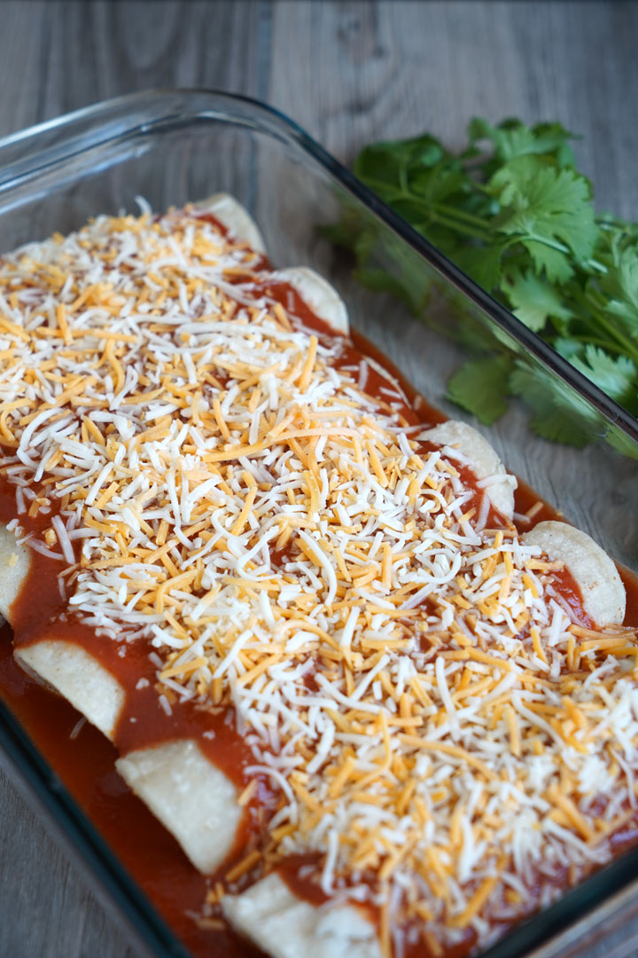 Uncooked cheese enchiladas in a tray.