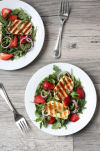 Top view- Grilled halloumi slices over a bed of arugula and strawberry salad on a white plate.