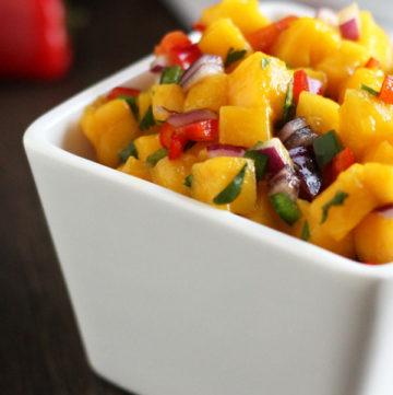 Mango salsa in a square white bowl.