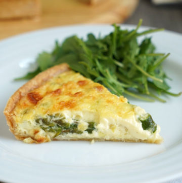 Slice of vegetable quiche with a side of greens on a white plate over a white napkin.