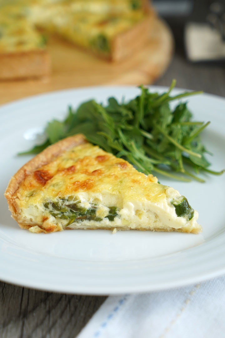 Slice of vegetable quiche and greens on a white plate over a white napkin.