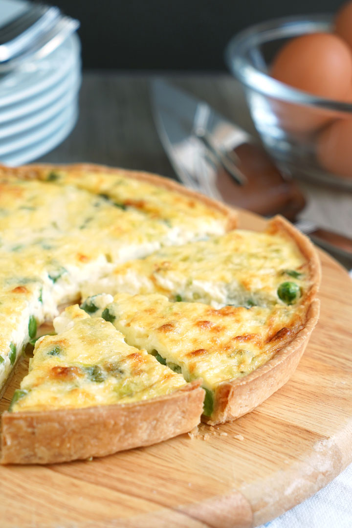 Vegetable quiche on a cutting board with pieces sliced.