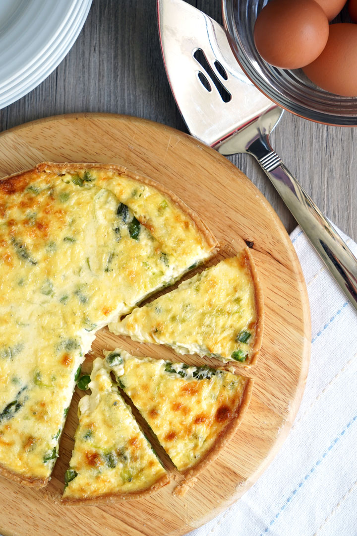 Top view of vegetable quiche on a cutting board with eggs and plates on  the side.