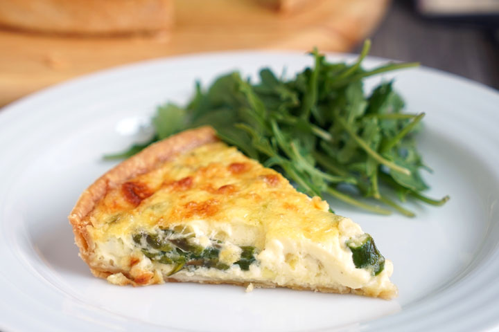 Slice of vegetable quiche with a side of greens on white plate.