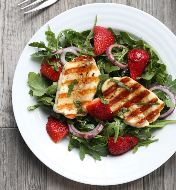 Grilled halloumi slices over a bed of arugula and strawberry salad on a white plate.