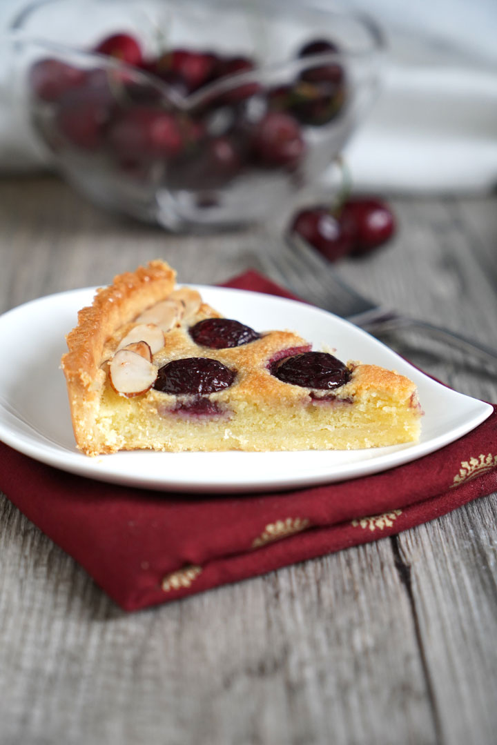 Slice of cherry tart with almond cream filling on a white plate and a red napkin with cherry bowl in the background.