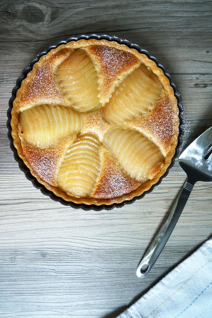 Overhead shot of pear and frangipane tart with spatula on side.
