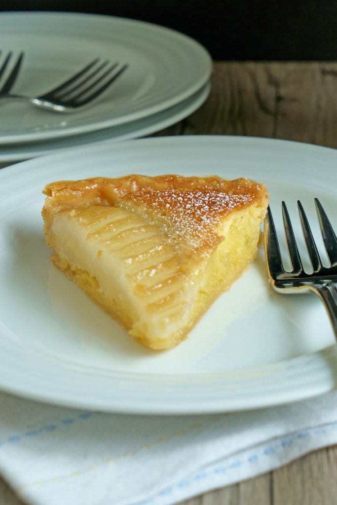 Slice of pear and frangipane tart in a white plate with a fork.