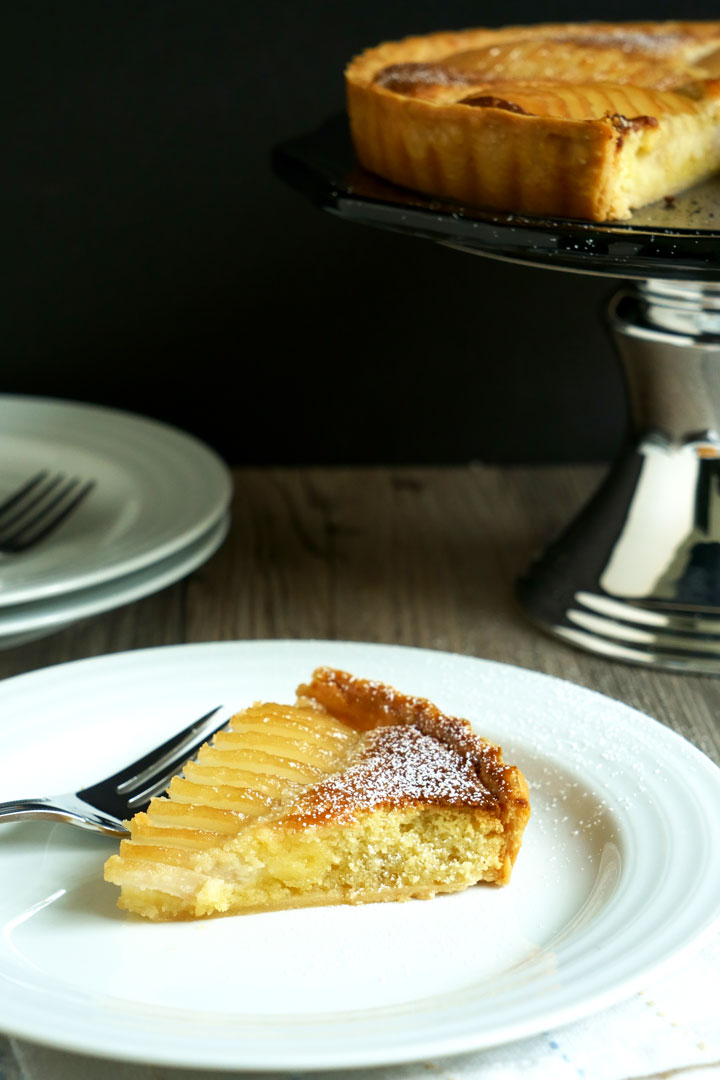 Slice of pear and frangipane tart on a white plate with fork and tart on cake stand in the background.