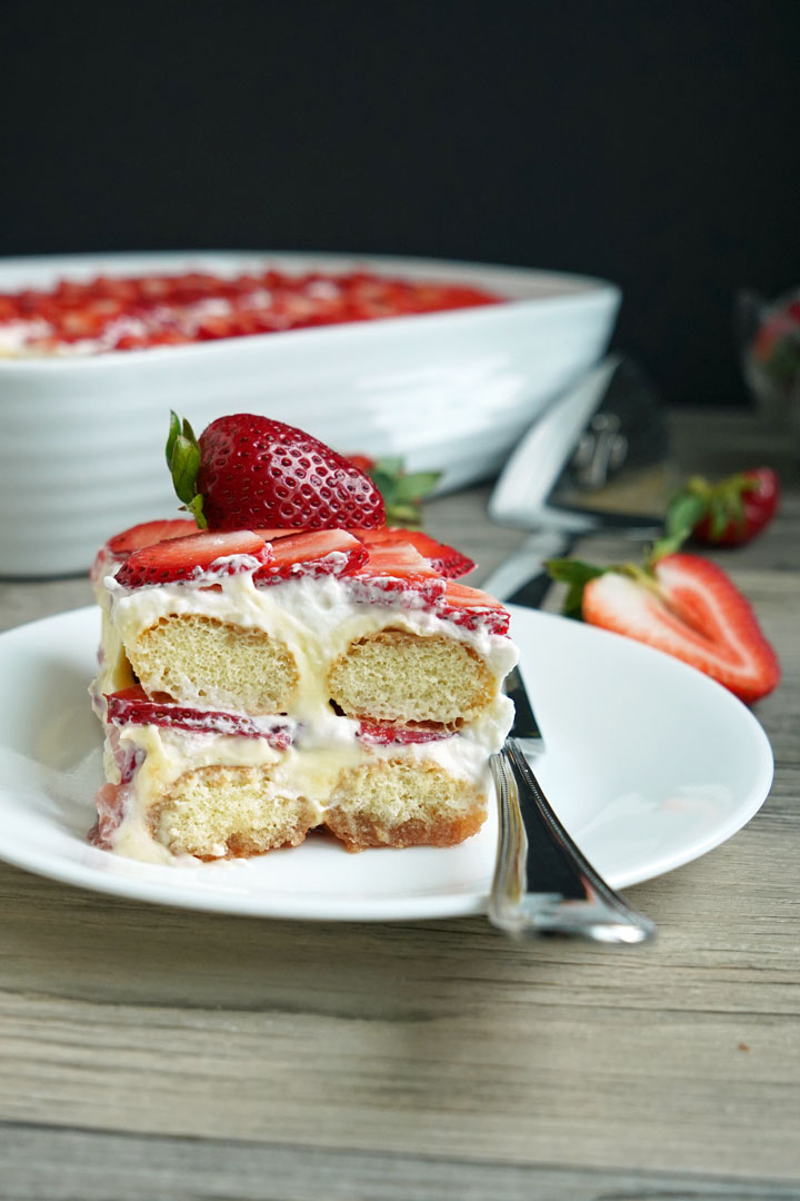 Slice of strawberry tiramisu on a white plate with fork. Strawberries and cake server in background.