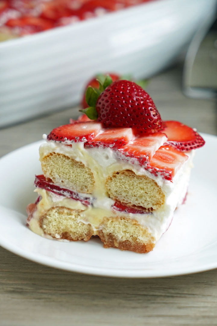 Close up of slice of strawberry tiramisu on a white plate.