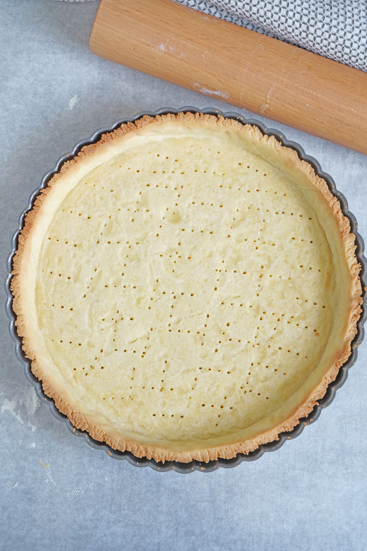Top view of empty baked tart crust with rolling pin on the side.