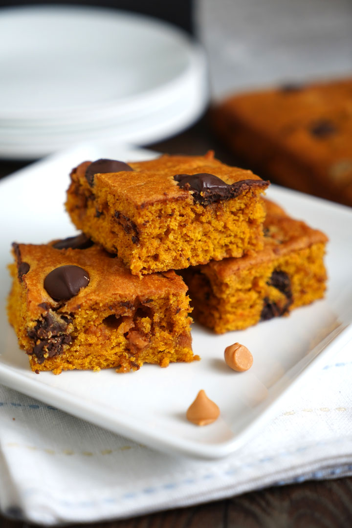 Three butterscotch pumpkin cake bars on a white plate over a napkin.