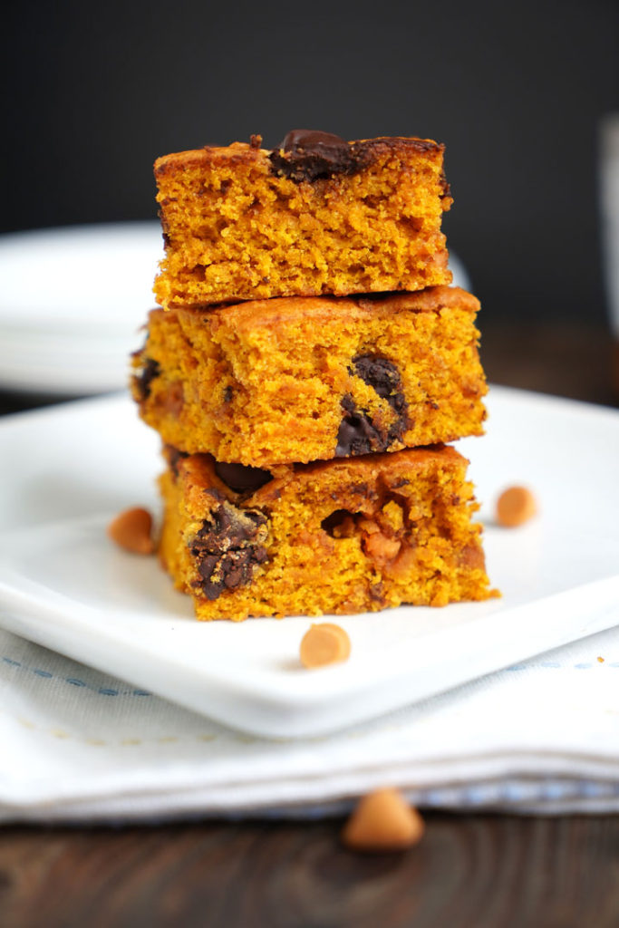 Three butterscotch pumpkin cake bars stacked on top of each other on a white plate.