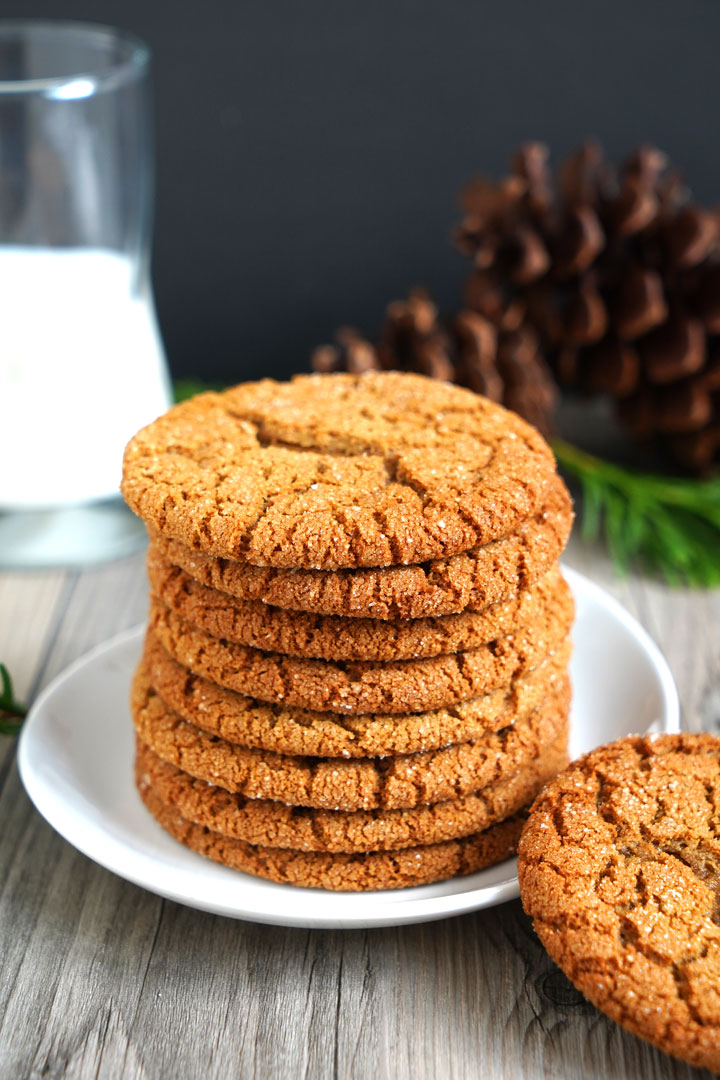 Stack of gingersnap cookies on a white plate with milk glass in the background.