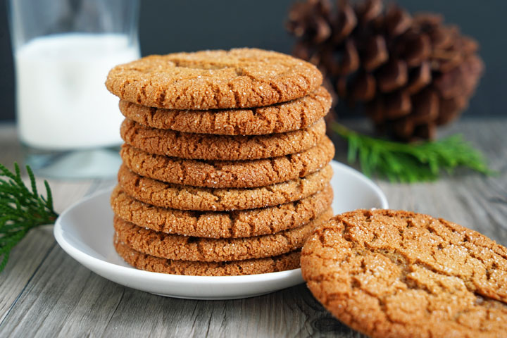 Stack of gingersnap cookies with one cookie off of plate and milk glass and pine cones in the background.