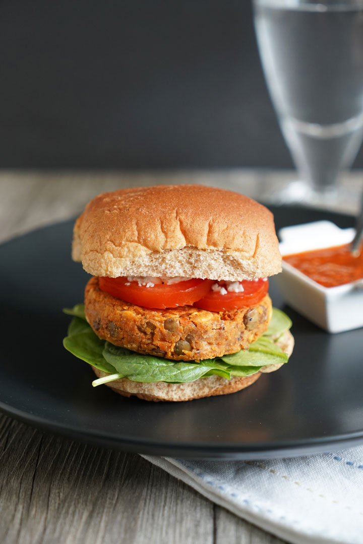 Lentil burger in whole wheat patty with tomato, lettuce on a black plate with harissa dressing on the side.