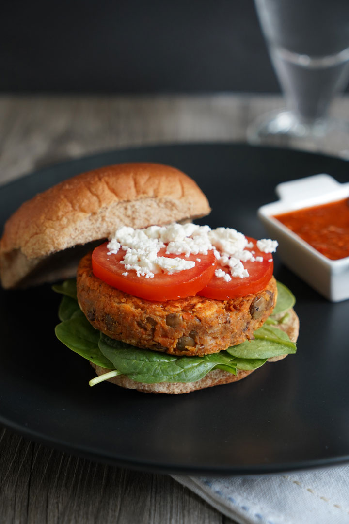 Open lentil burger on whole wheat bun topped with tomato and feta.