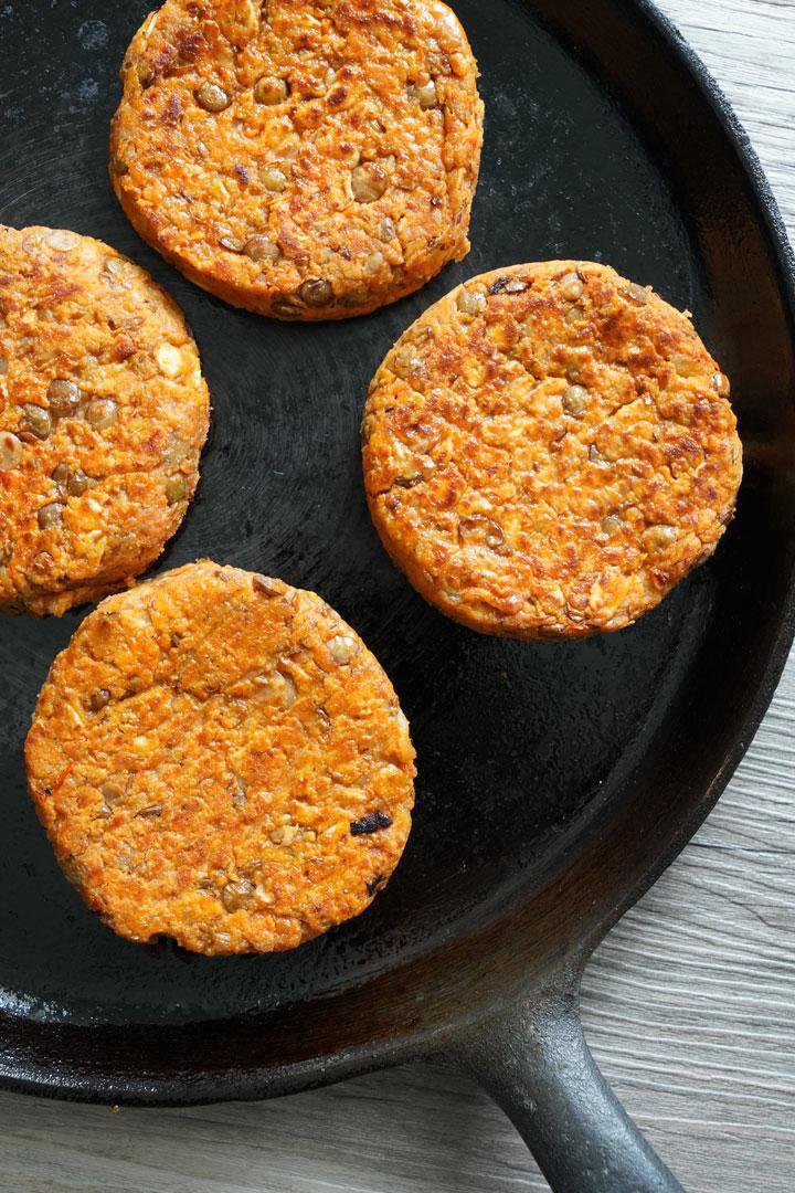 Lentil burgers cooking on a cast iron skillet.