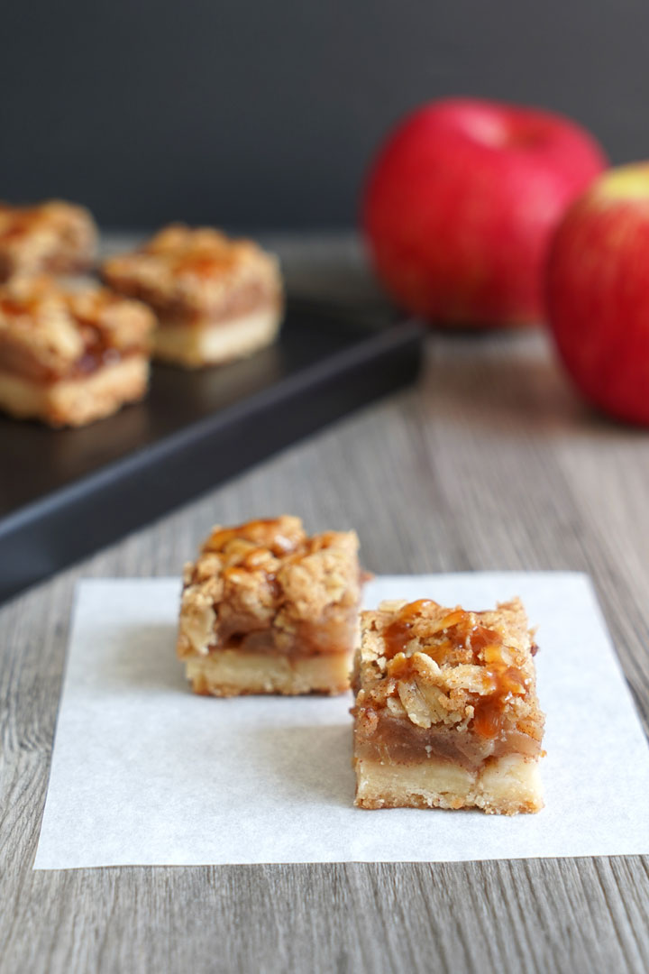 Two bite sized apple pie bars on a piece of parchment with more bars  and apples in the background.
