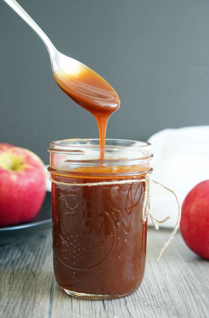 Caramel sauce dripping off a spoon into a glass jar of more sauce.