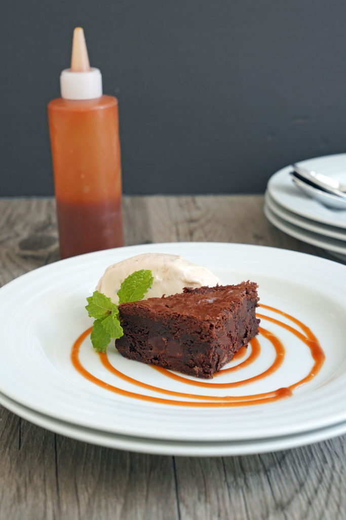 Plated brownie with ices cream using caramel sauce for decoration.